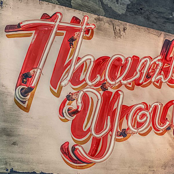 "A neon sign reading ""Thank You""."